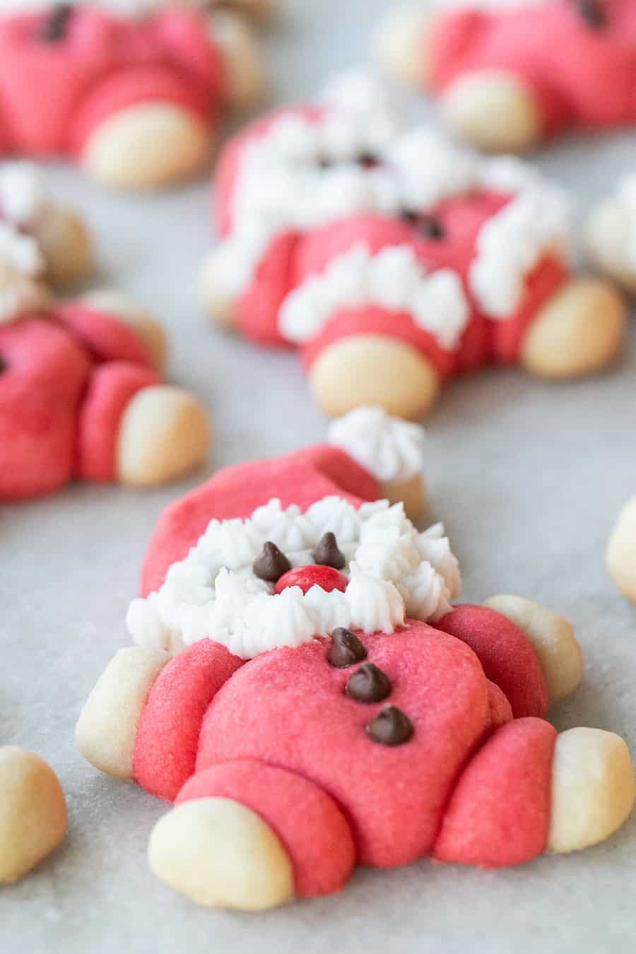 Santa cookies with chocolate chip eyes and a fluffy white beard.