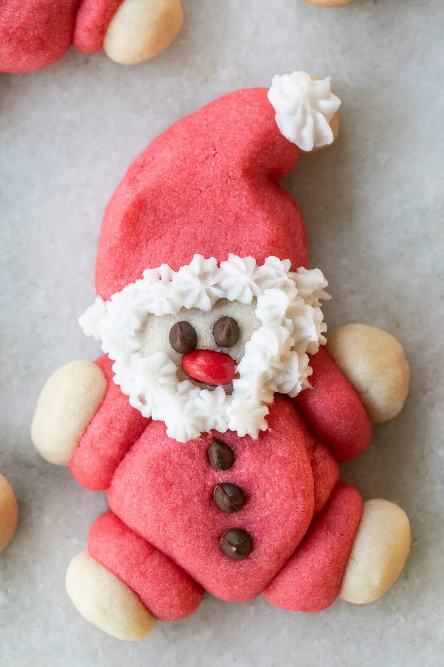 Santa Cookie shaped at santa made with chocolate chip eyes, red hot nose and fluffy white frosting for a beard.