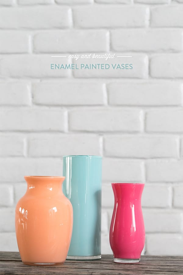 Orange, blue and pink vases on wooden table.
