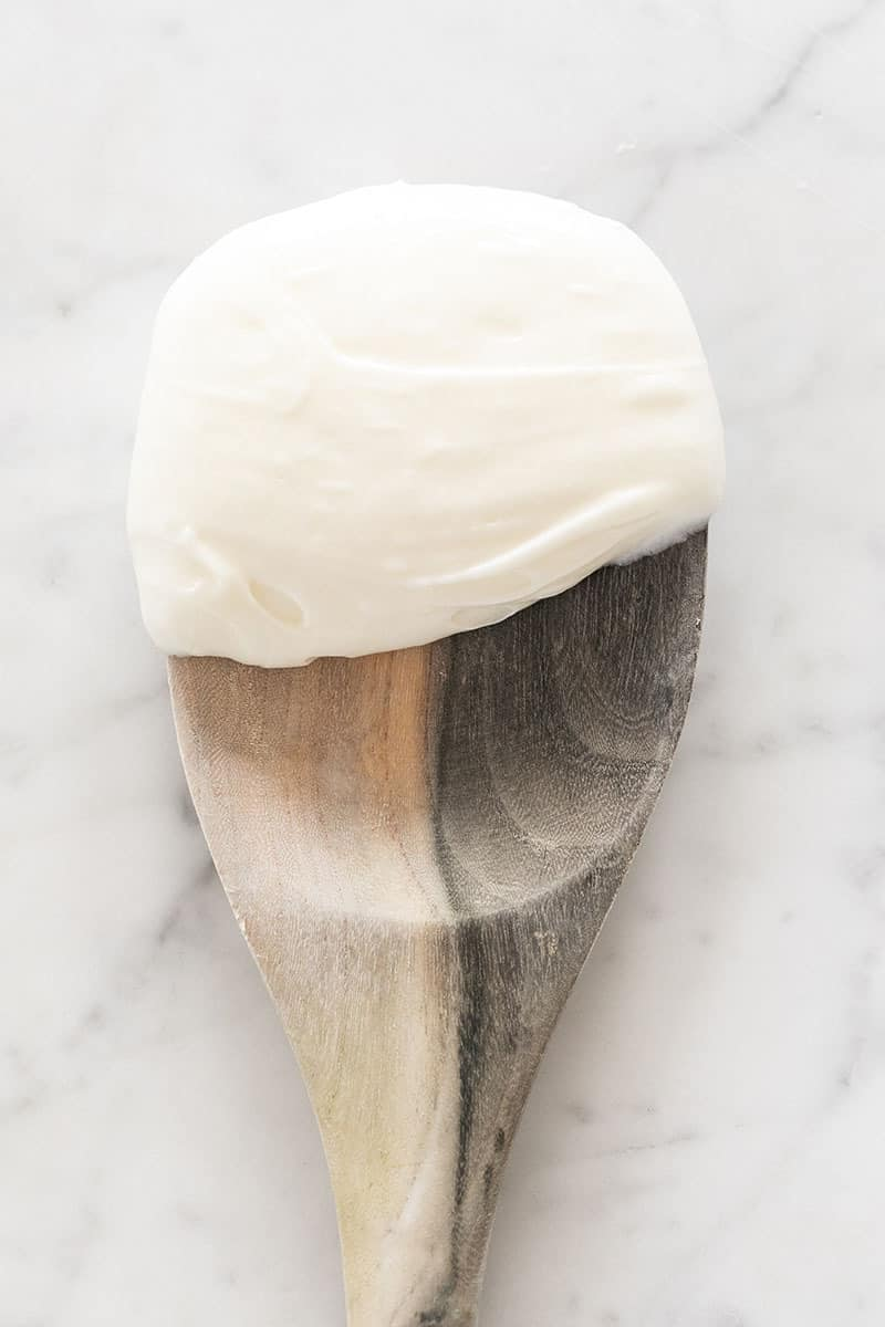 Cream cheese frosting on a wooden spoon.