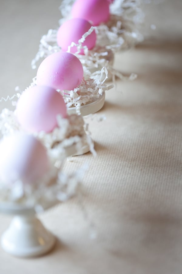 Ombre Easter eggs on mini cake stands with crinkle paper.