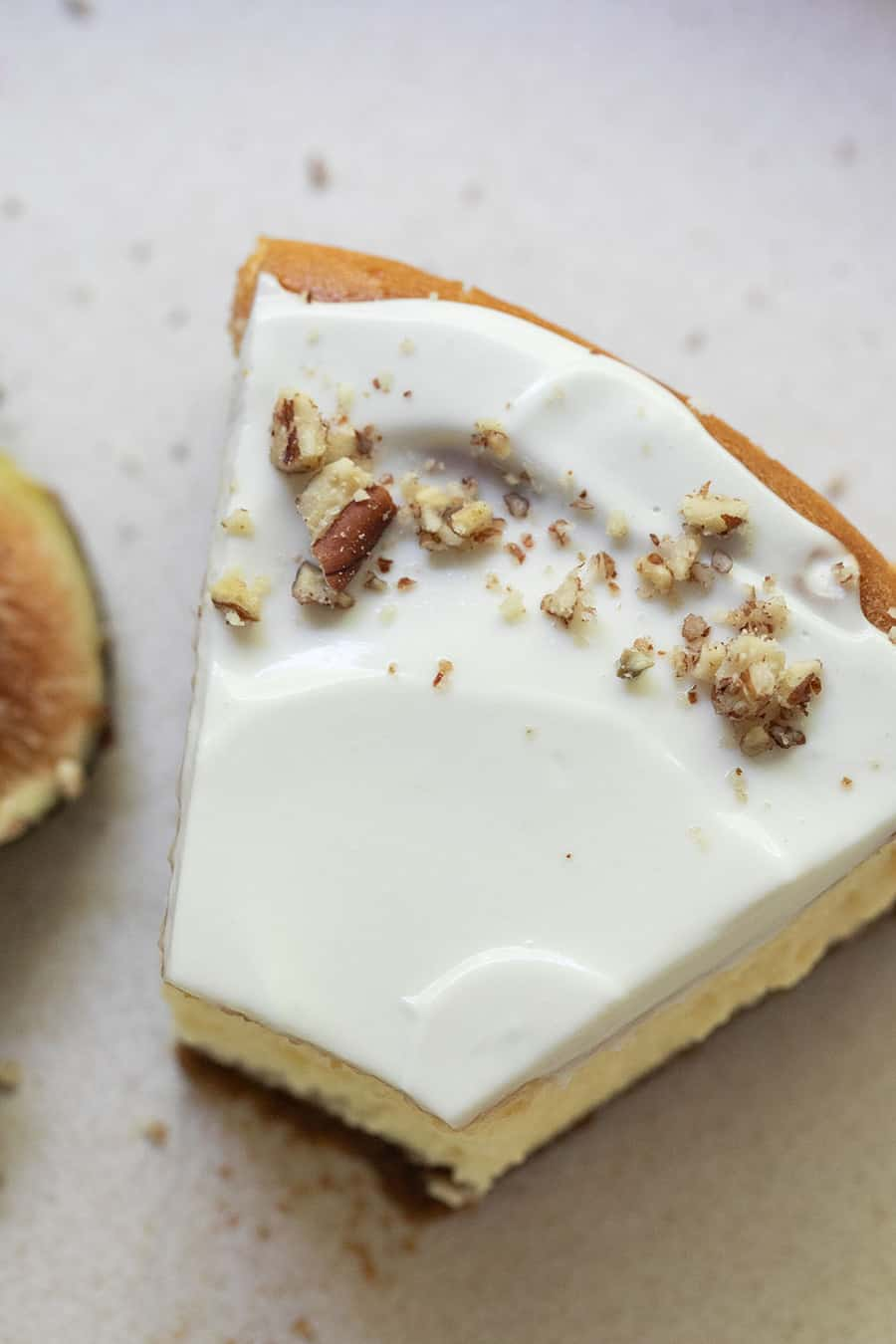 Slice of cheesecake with crushed walnuts and sour cream topping