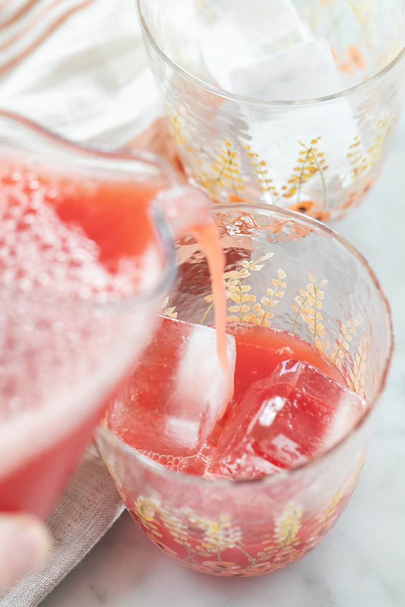 Pouring watermelon juice over ice cubes.