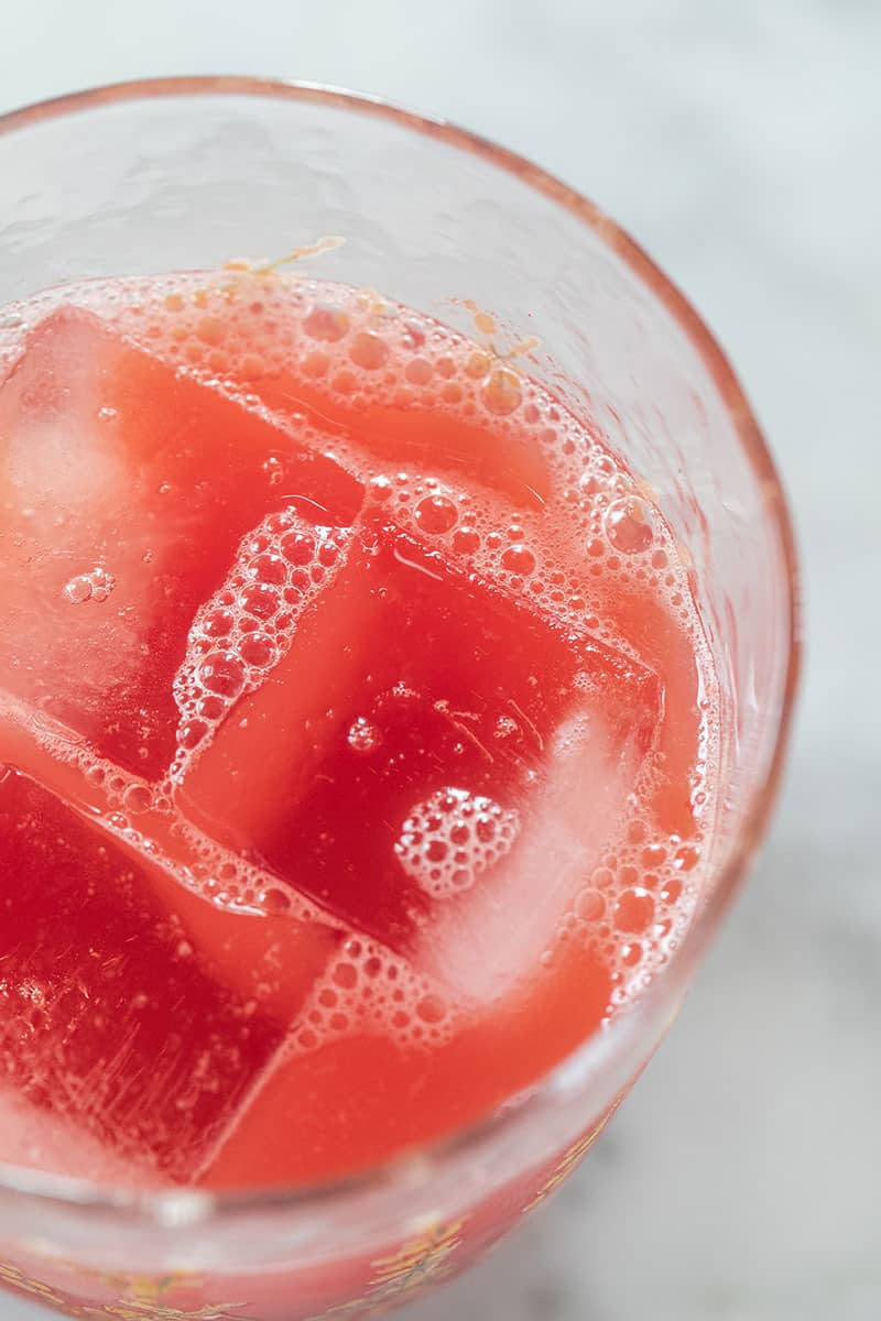 Watermelon juice in a glass with large ice cubes.