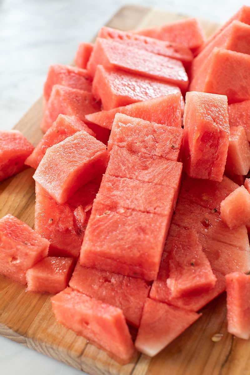 Watermelon cut into cubes on a cutting board.