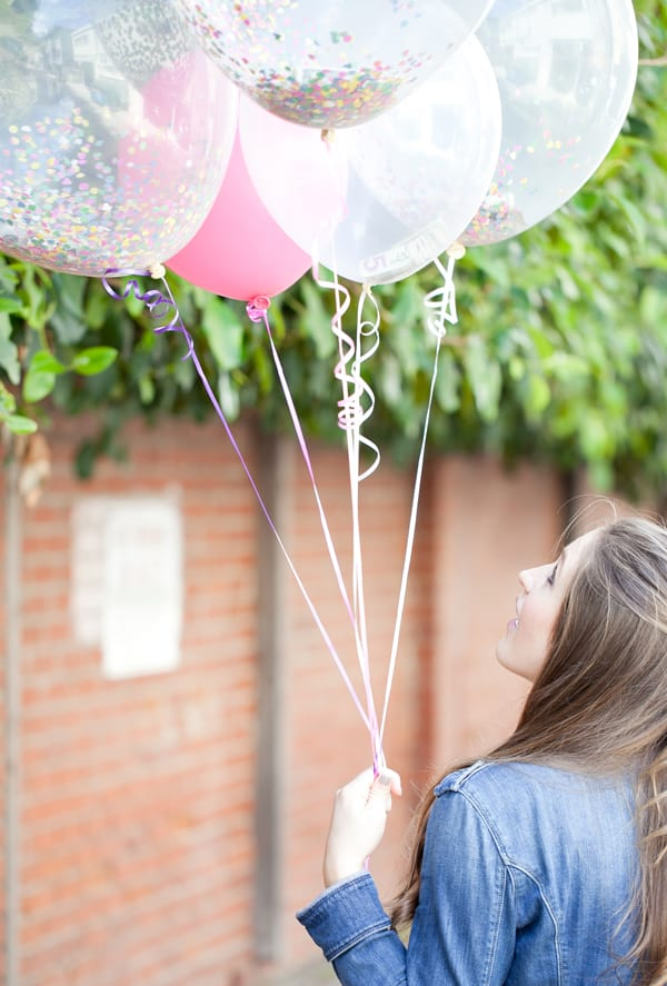 Girl holding 5 balloons filled with money and confetti.
