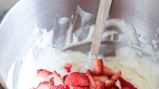 Foling in strawberries to a whipped bowl.