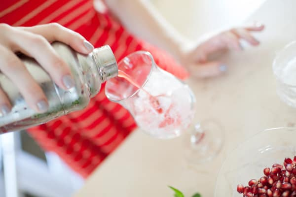 Side shot of strawberry mojito being poured into a glass