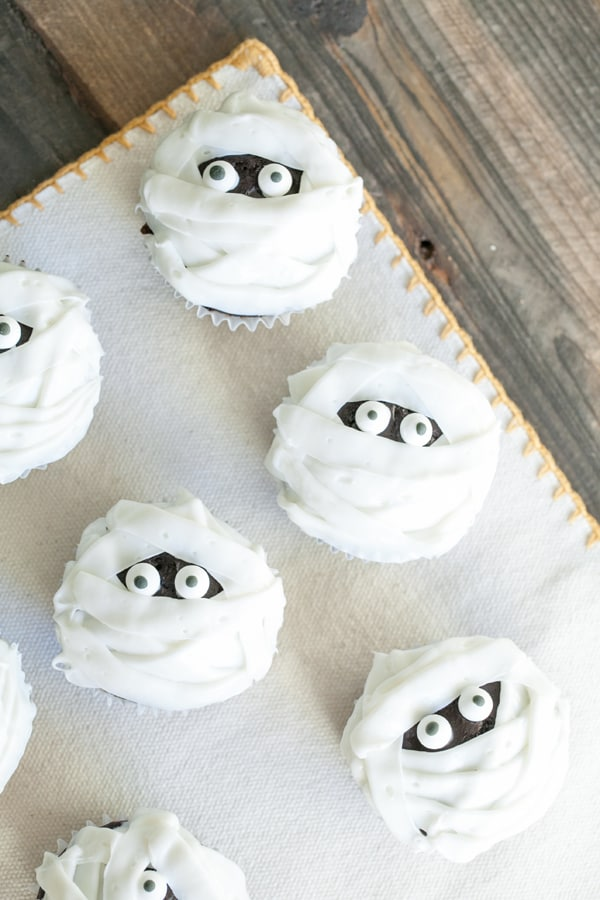 Mummy cupcakes with eyes on a table.