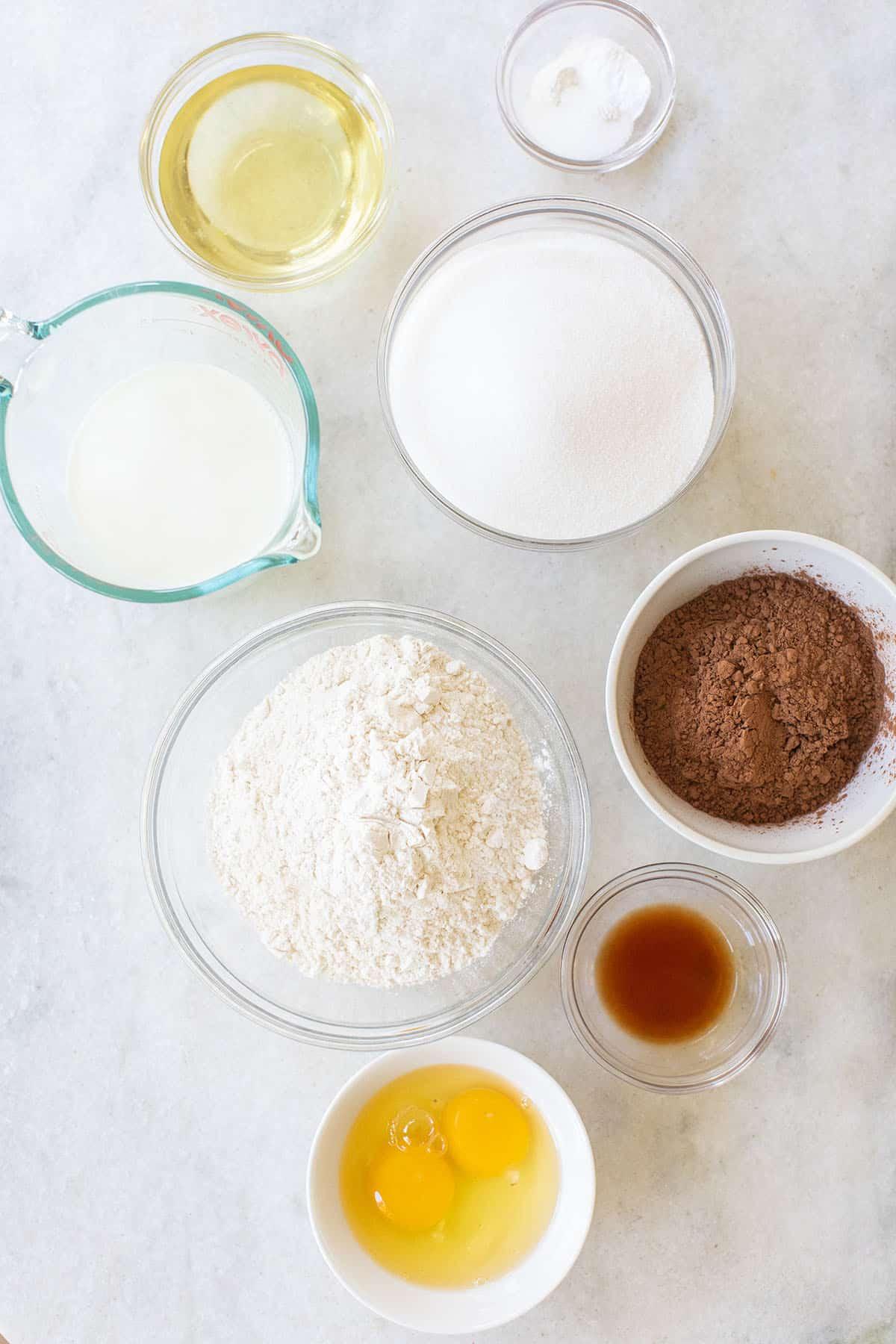 oil, flour, sugar, cocoa powder, eggs, milk, vanilla extract and baking soda and baking powder in small bowls