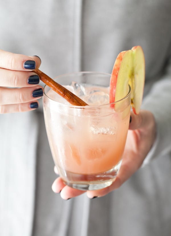 shot of hands holding apple cider cocktail