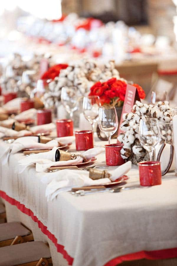 Rustic Christmas table setting with red enamel cups and red flowers.
