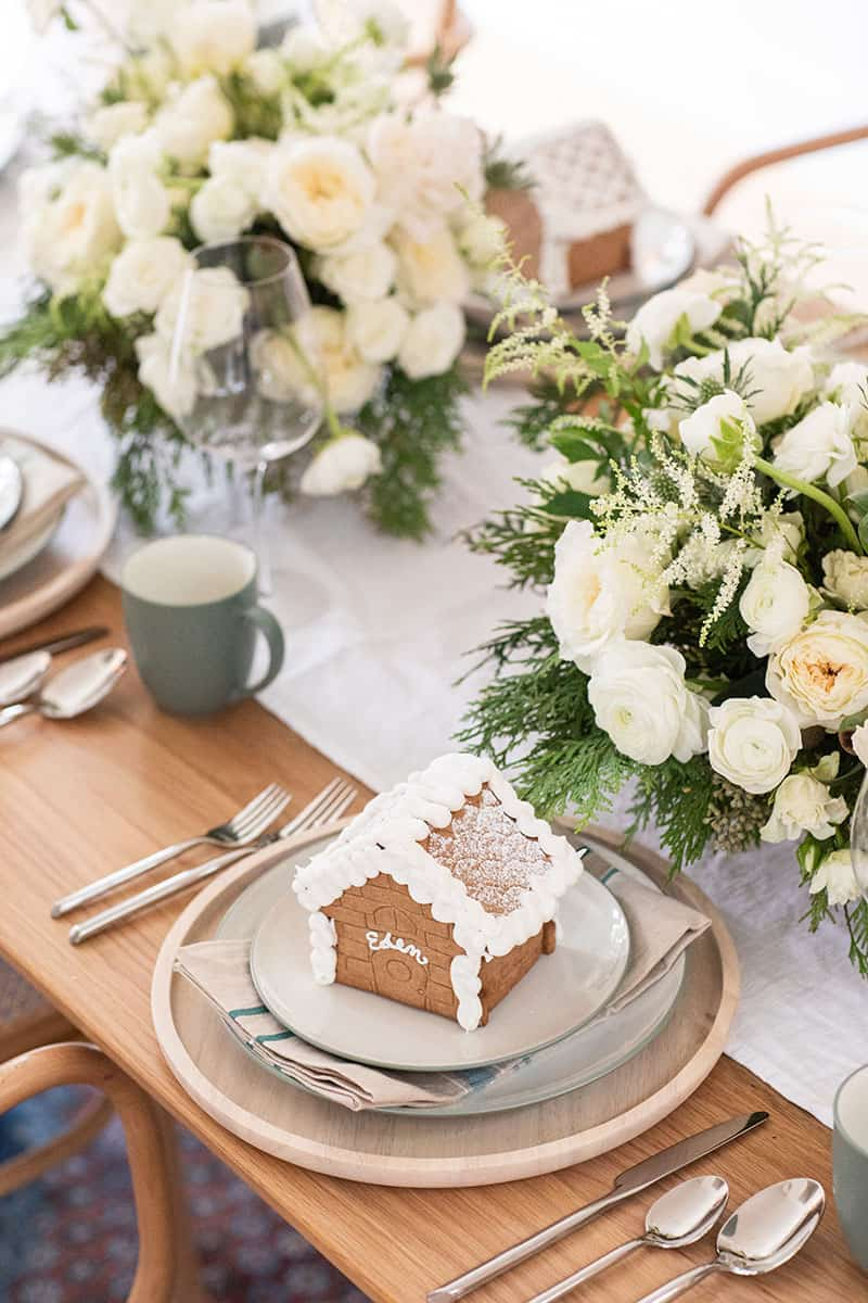 Gingerbread house on a table with white flowers