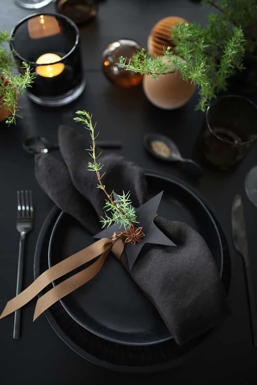 Dark and moody black table setting with black napkins and gold accents.