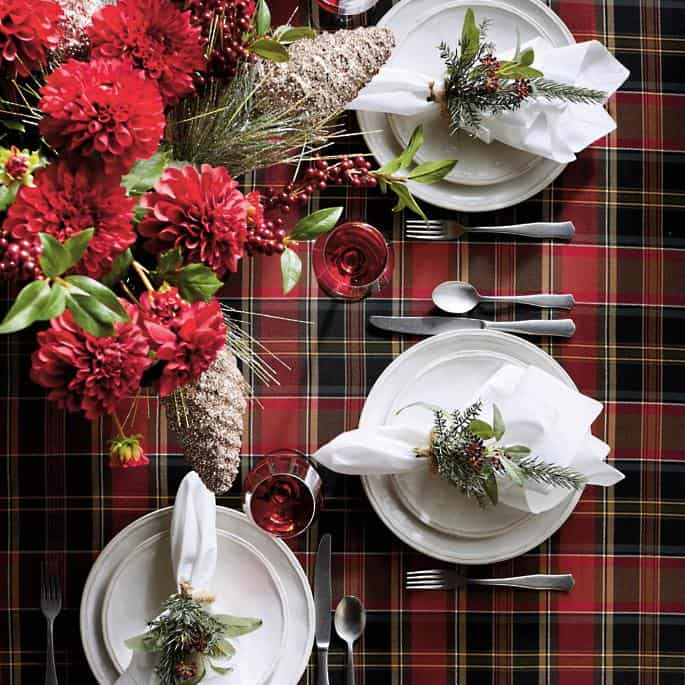 Plaid table setting for Christmas with red and green flowers.