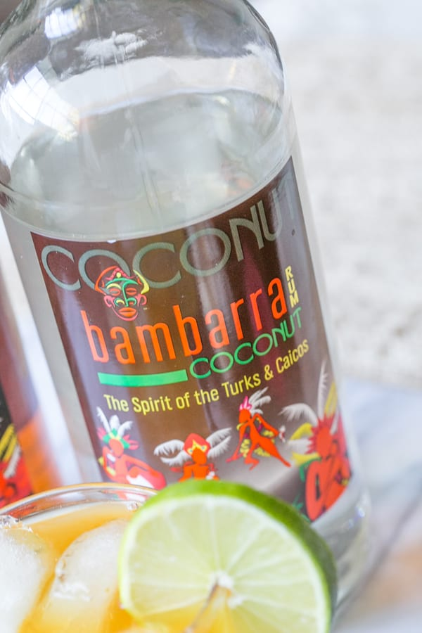 A side on shot of a bambarra bottle of rum and a glass of rum