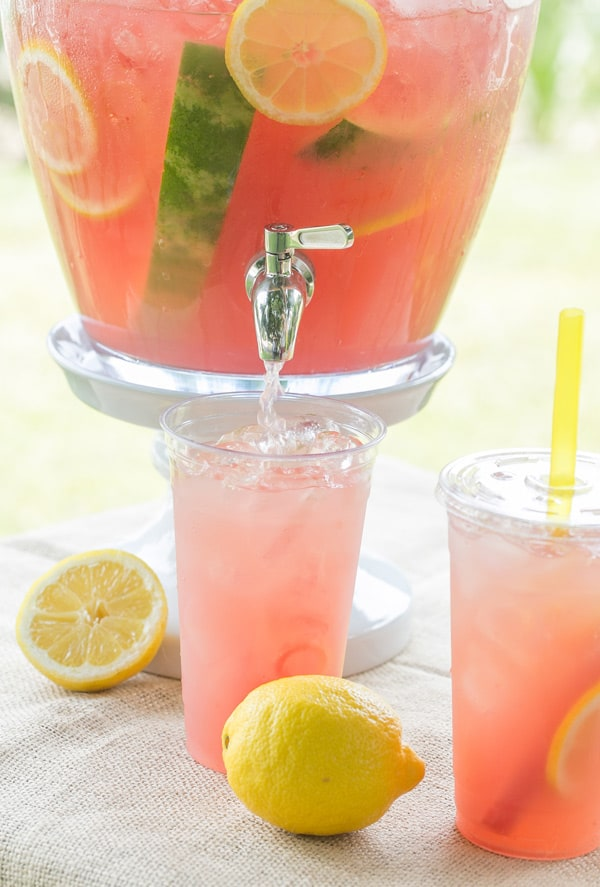 Watermelon lemonade being poured into a plastic cup.