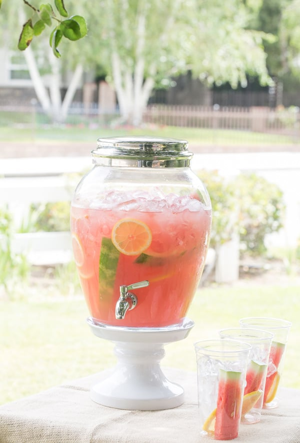 Large batch of watermelon lemonade in glass jar with watermelon and lemons.