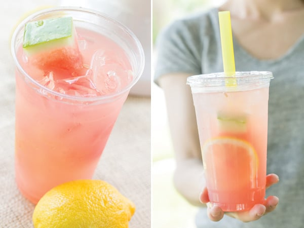 Watermelon Lemonade in plastic cup with lemon and hand holding the cup.