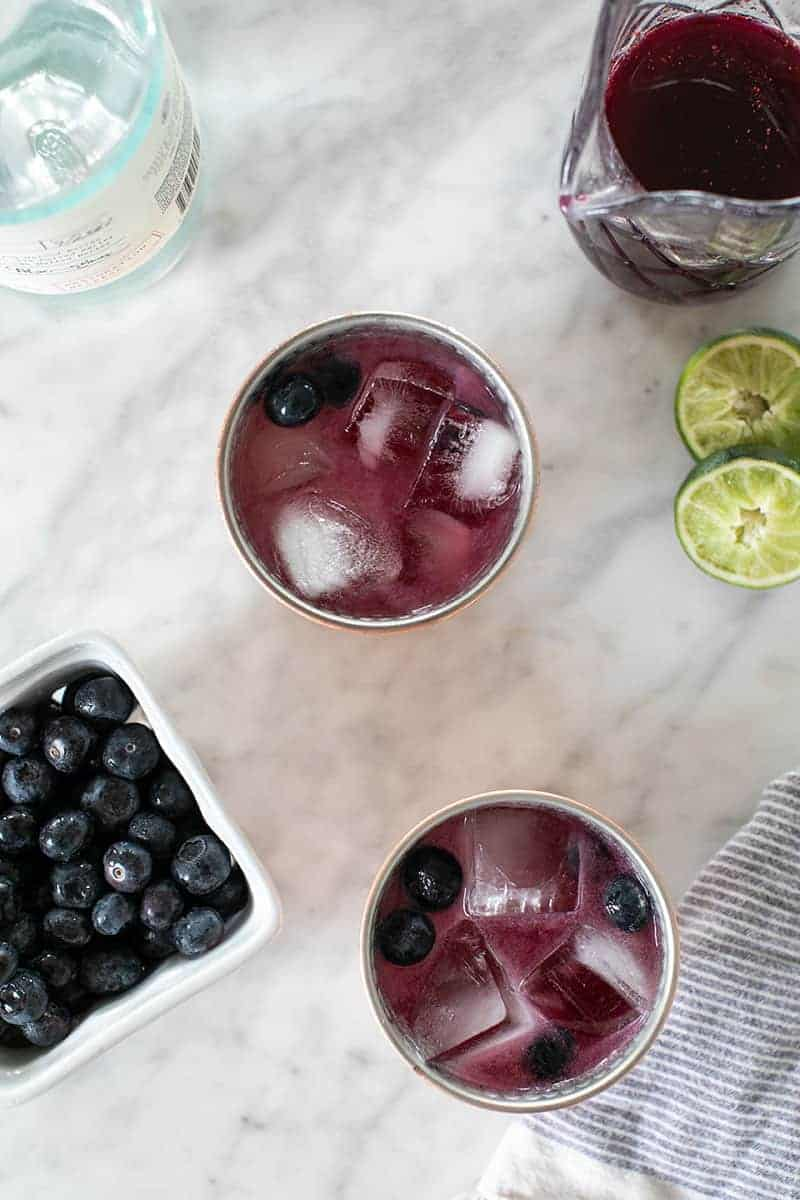 Blueberry Moscow Mules on a marble table with lime and fresh blueberries.