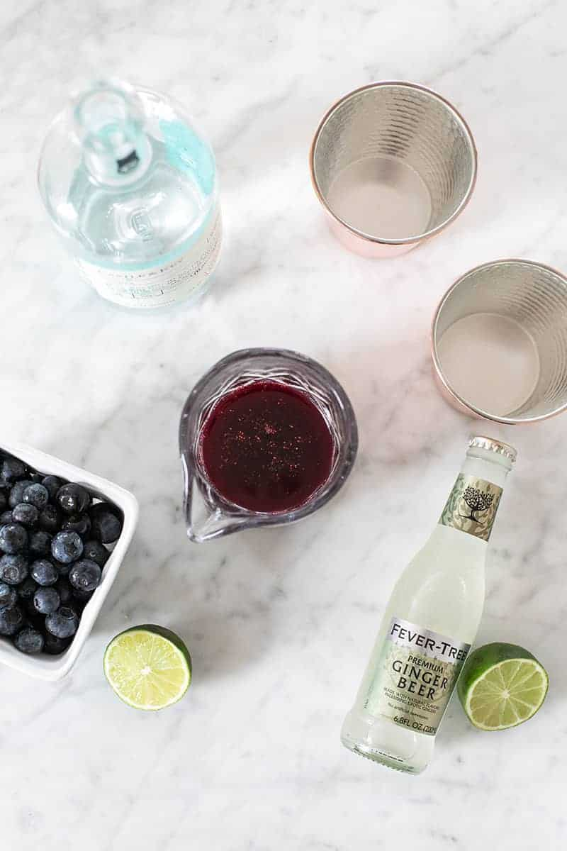 Ginger beer, blueberry syrup, blueberries, limes on a marble table.