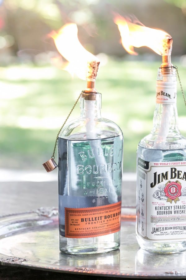Glass bourbon and Jim Beam bottles with tiki torch hardware and fire.