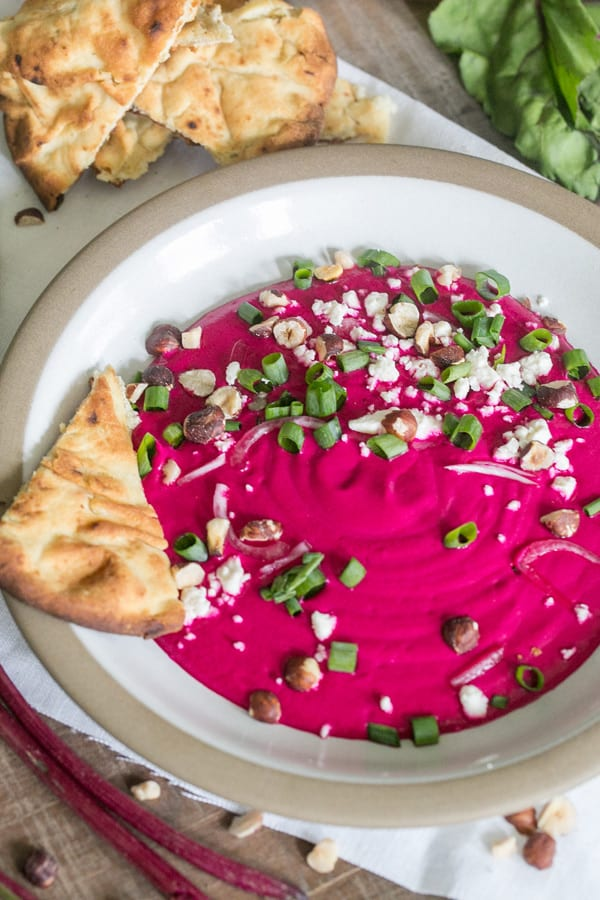 beet dip in a bowl with pita bread