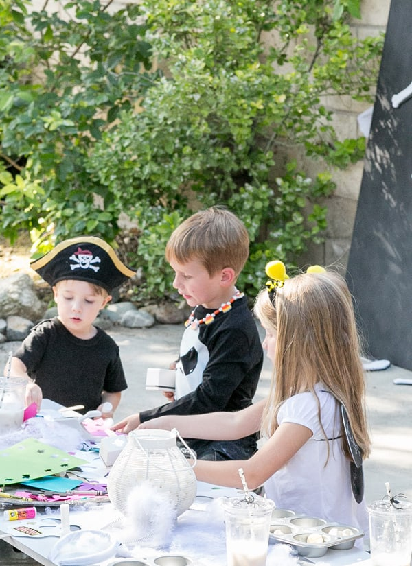 shot of kids around a table playing with kids halloween party ideas