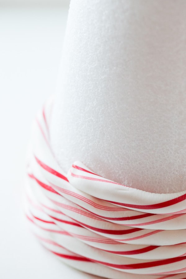 Warm candy canes being wrapped around a styrofoam cone.