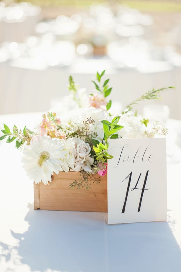 DIY wedding flowers in a wooden box with a table number.
