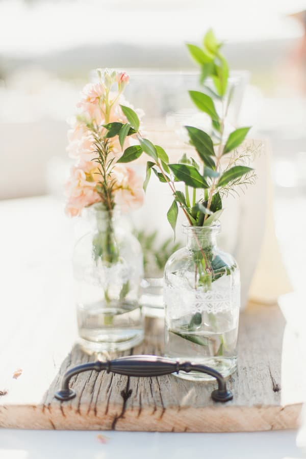 Simple wedding flower arrangements in glass vases on a wooden board.