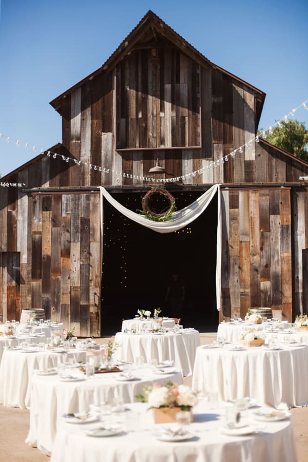 Beautiful barn with white tables and flowers.