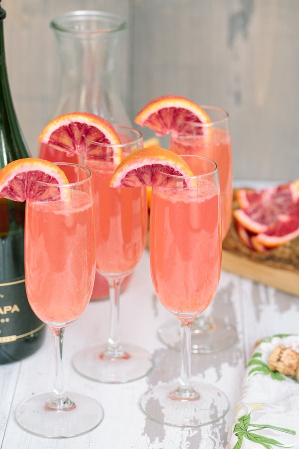 Four glasses pink mimosas on wooden board.