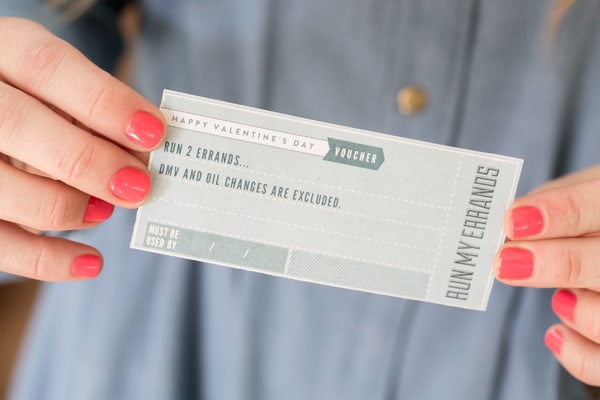 Eden Passante holding a Valentine's Day printable voucher.
