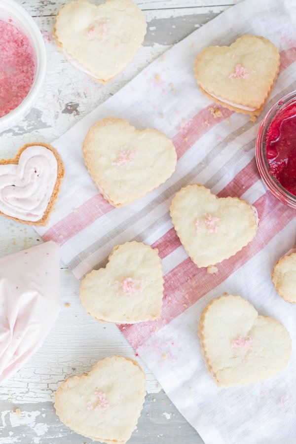 Heart shaped raspberry shortbread cookies with a raspberry white chocolate filling on a pink towel.