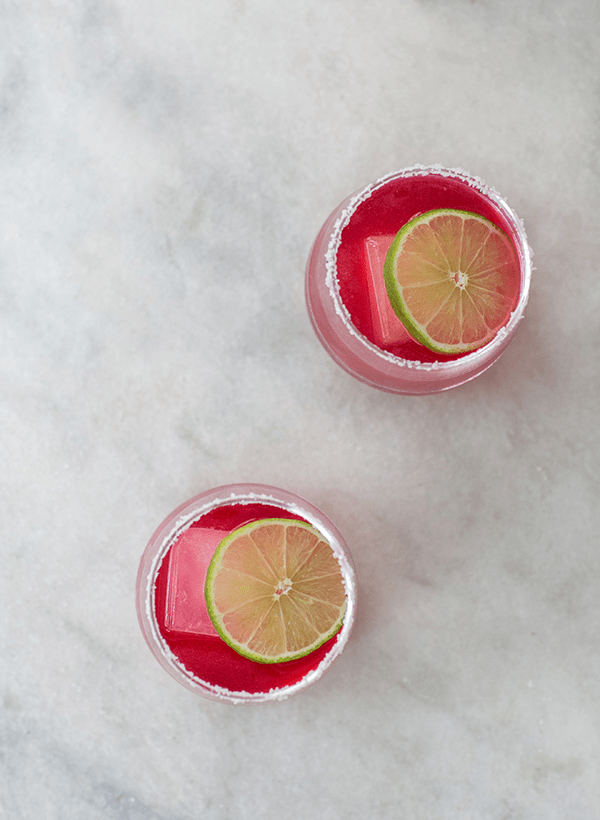 Two pink hibiscus margaritas on a marble table.
