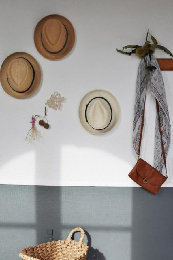 Gray and white wall with hats on the wall