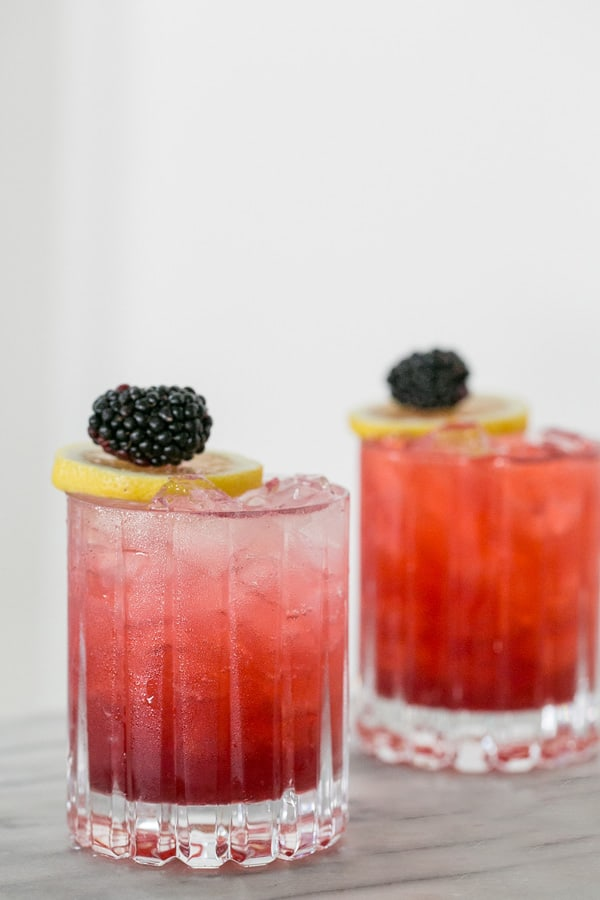 shot of drink in glass garnished with blackberries