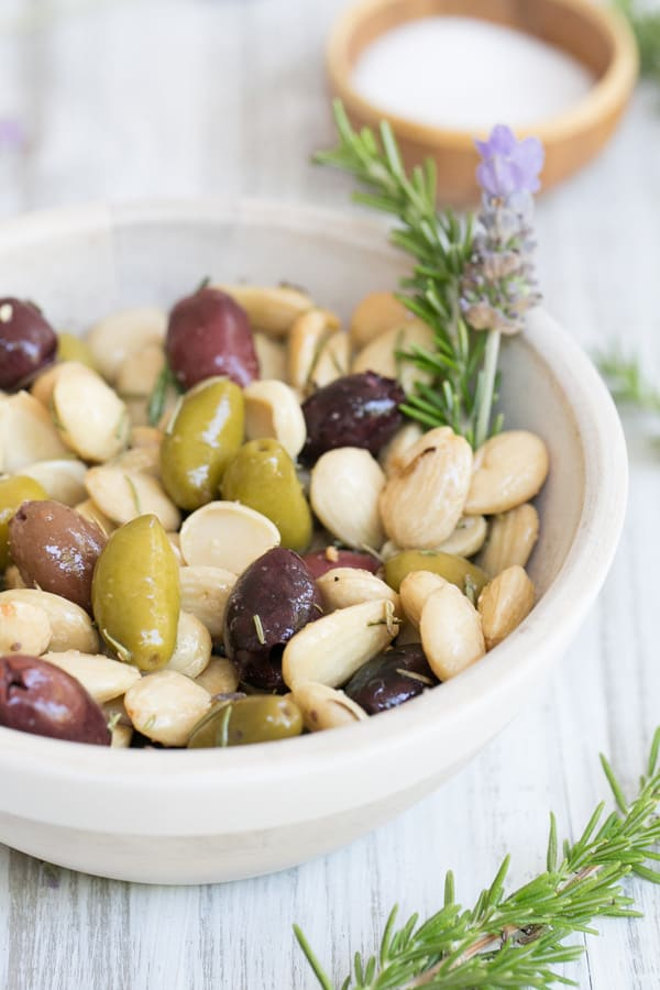 Marcona Almonds with olives, rosemary and lavender in a small bowl.