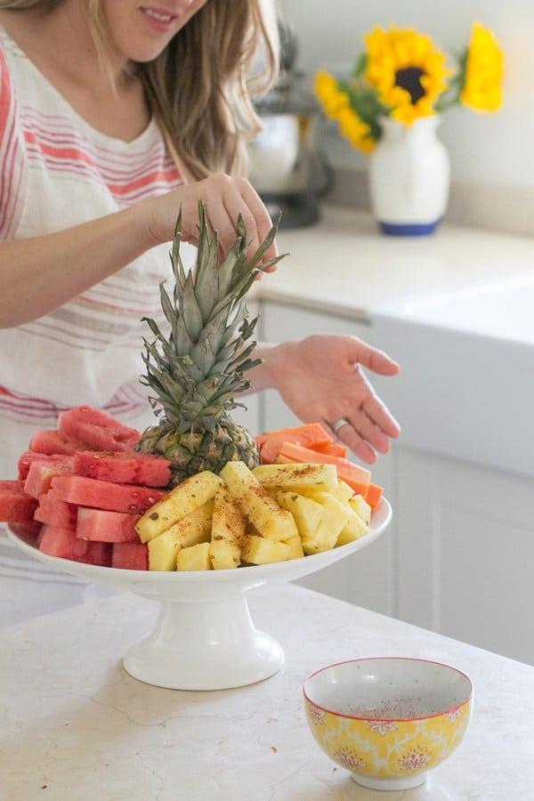 Girl sprinkling chili lime salt on pineapple, watermelon and mango.