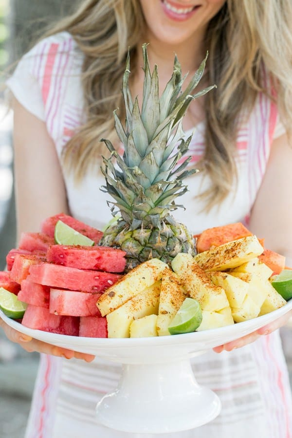 Girl holding platter of pineapple, watermelon and mango with chili lime salt sprinkled on the fruit.