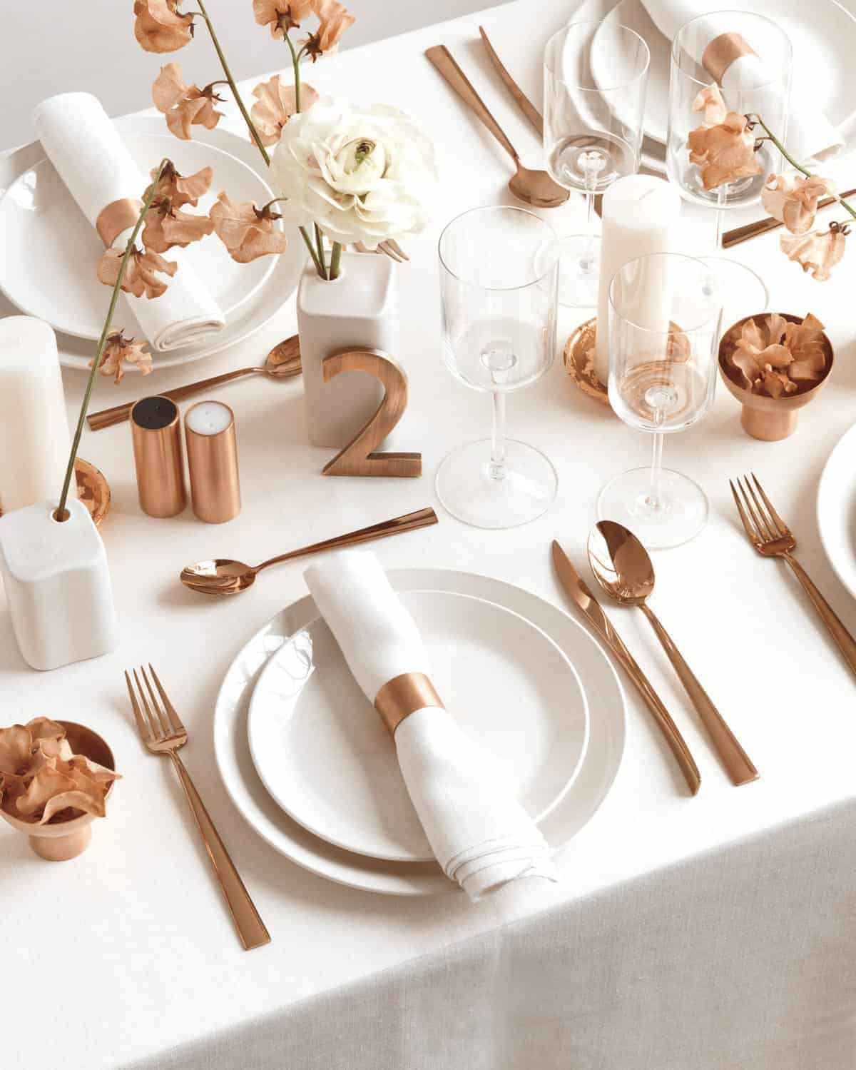 White and copper table setting. White plates and copper flatware.