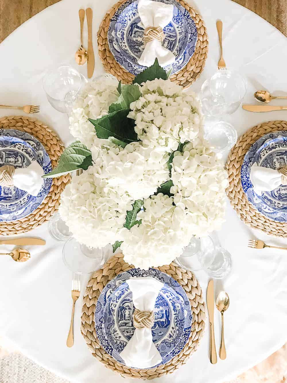 White hydrangeas and classic blue and white plates with woven chargers.