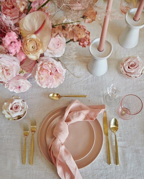 Pink and white table setting with pink plates and gold flatware