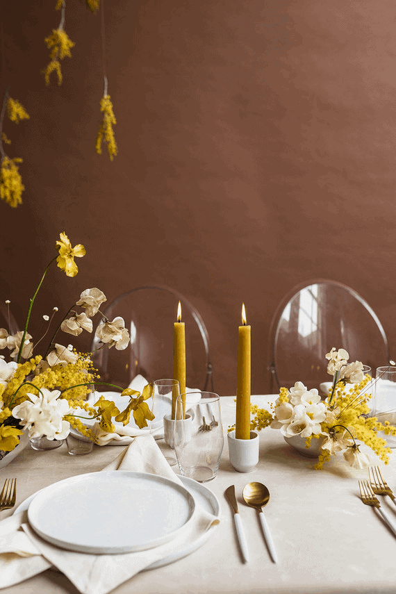 Yellow, white and gold table setting with white plates and gold flatware.