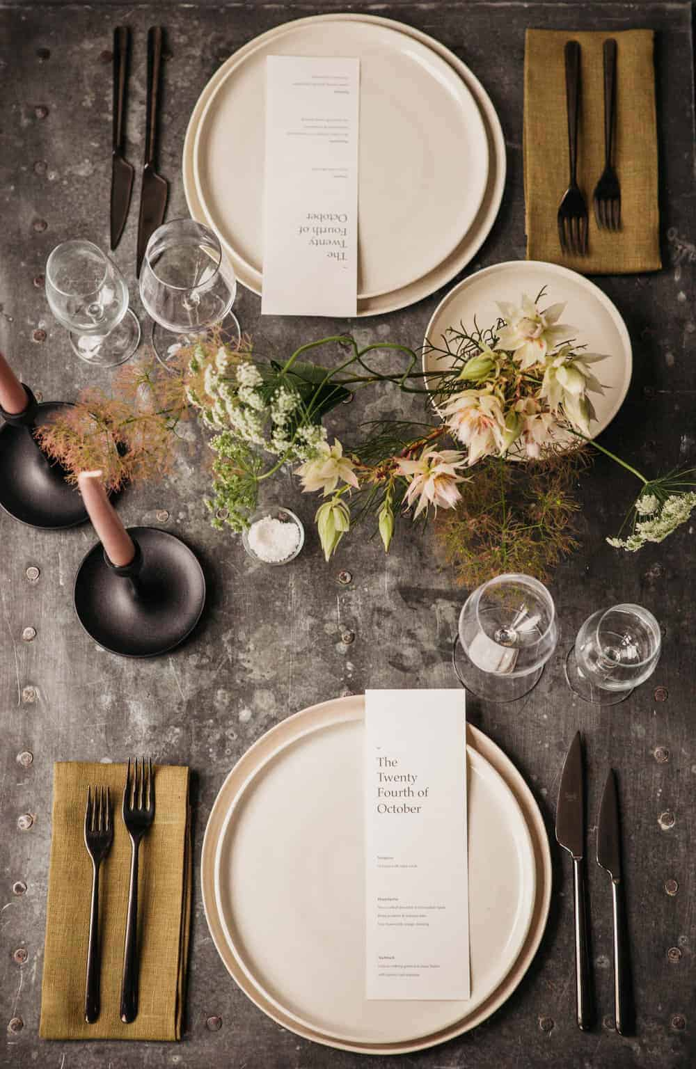 Moody Black table setting with pink plates and flowers.