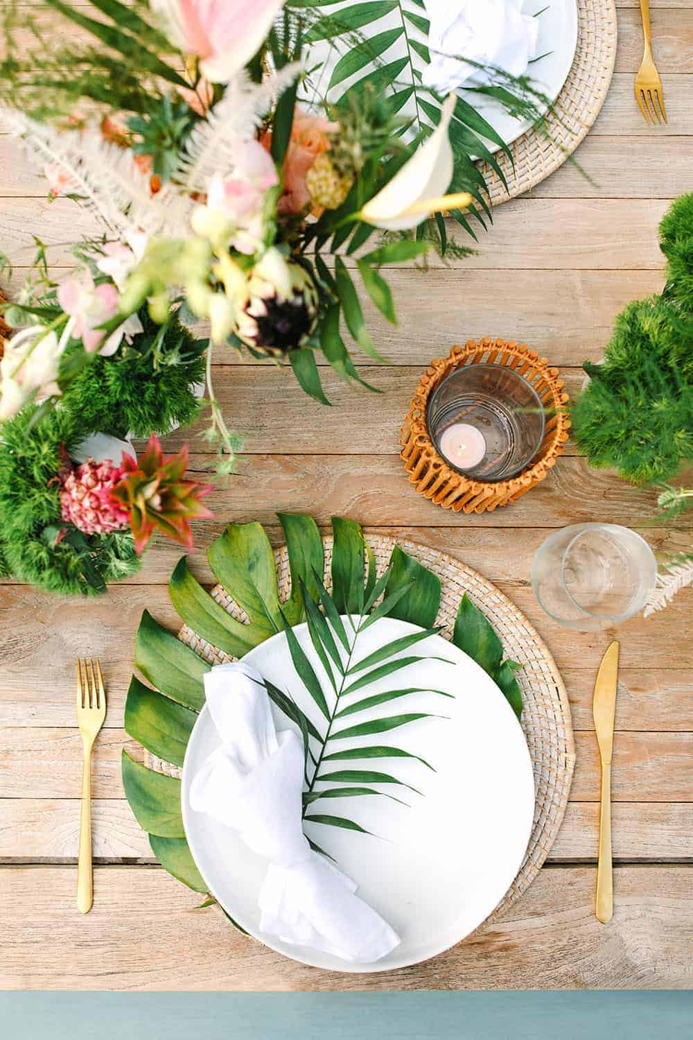 Tropical table setting with giant palm leaves, white plate and woven charger.