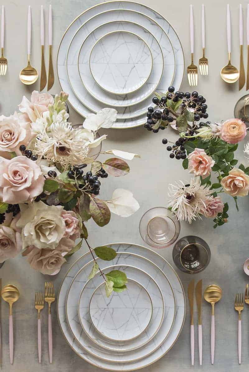 Marble plates with pink flowers and gold and pink flatware with wine glass and pink flowers on a great table.