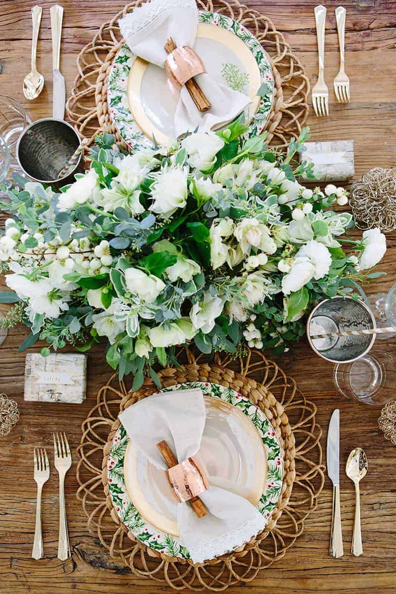 Green and white holiday table setting with rustic wood table.