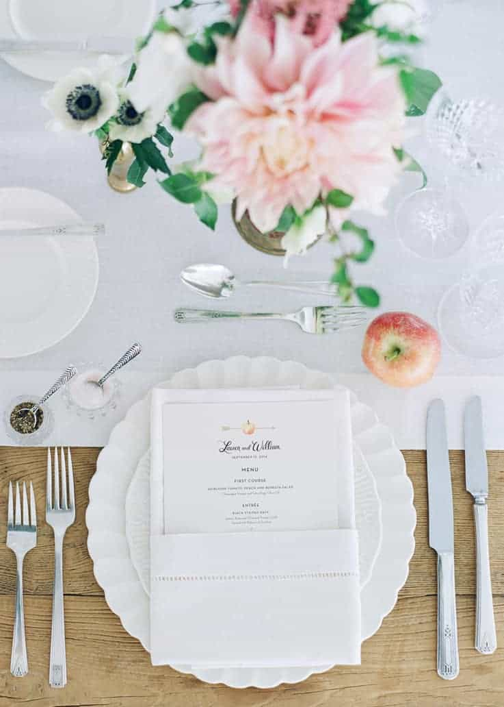 Table setting with riffled white plates, silver flatware, simple pink flower and one apple.